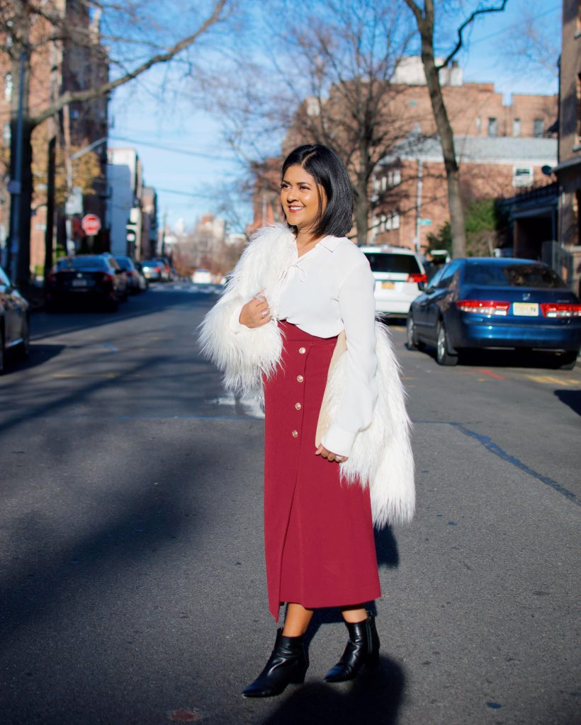 white faux fur coat with red midi skirt